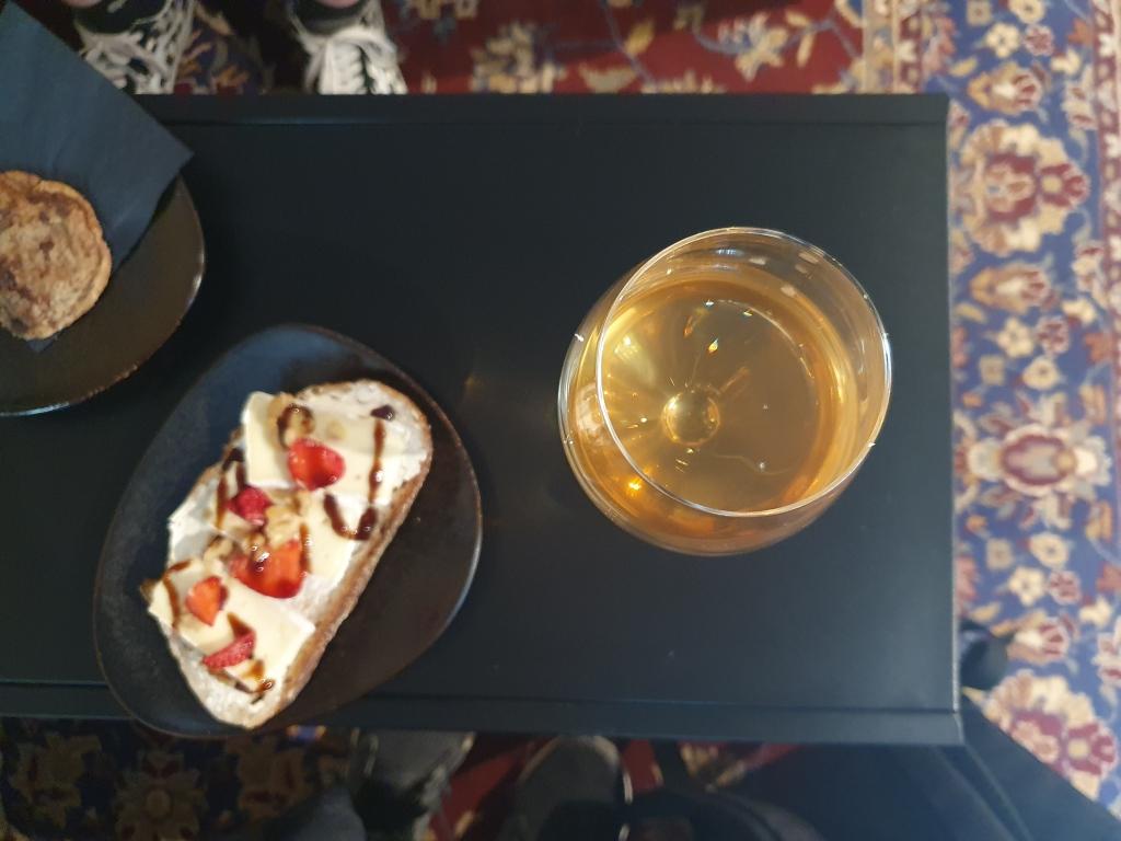 Kahiwa Coffee & Wine pöydällä lasillinen natuviiniä ja juurileipä brie-juustolla ja mansikoilla.